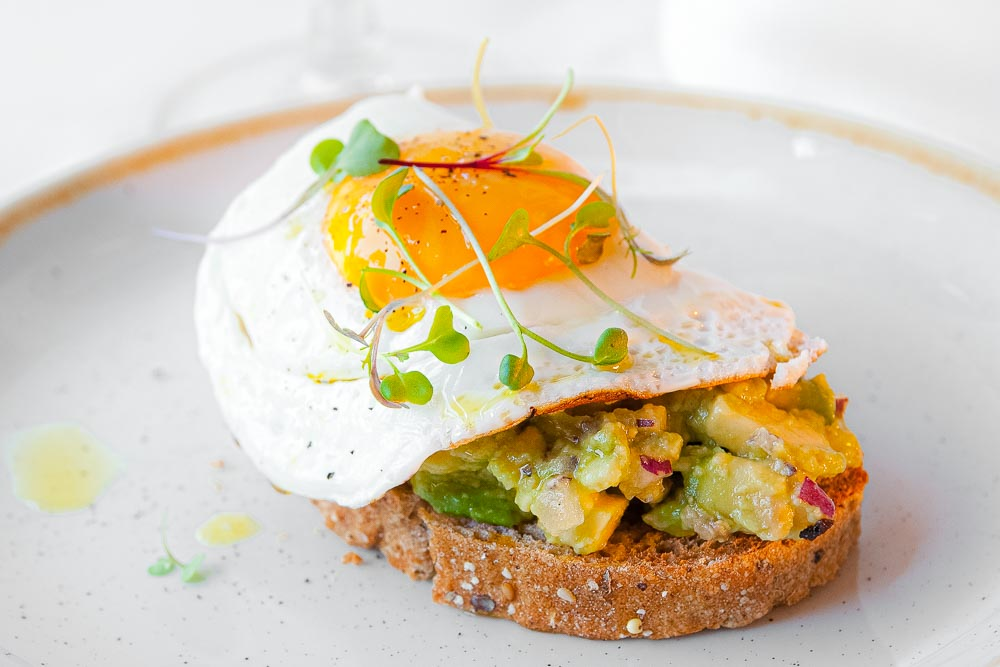 Homemade avocado tartar on toast, grilled egg and fresh chives (vegetarian)
